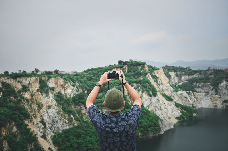 Man photographing on mountains against sky