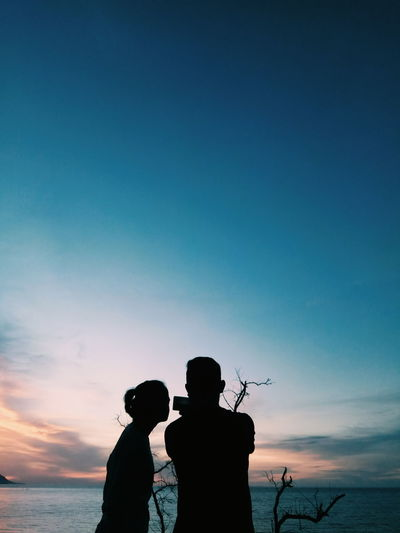 Silhouette Couple Standing At Beach Against Blue Sky