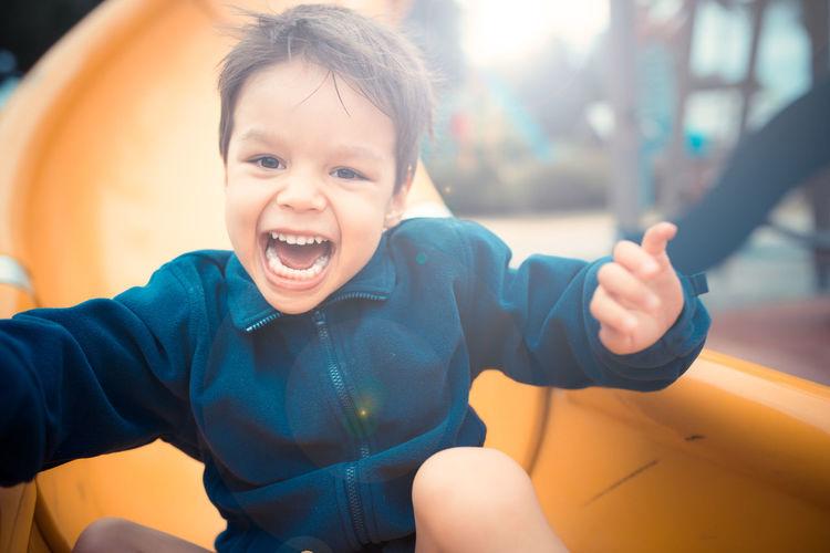 Portrait of smiling boy on slide