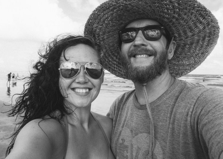 Portrait of smiling couple wearing sunglasses at beach