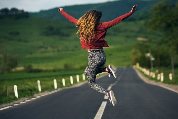 Young Woman Jumping On Road