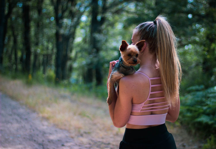 Rear view of woman with dog outdoors