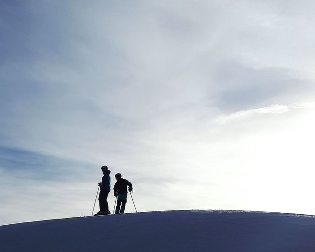 Silhouette Friends Skiing On Snow Against Sky During Sunny Day