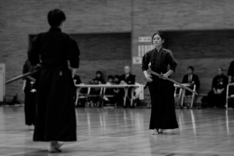 Full length of man and woman practicing kendo