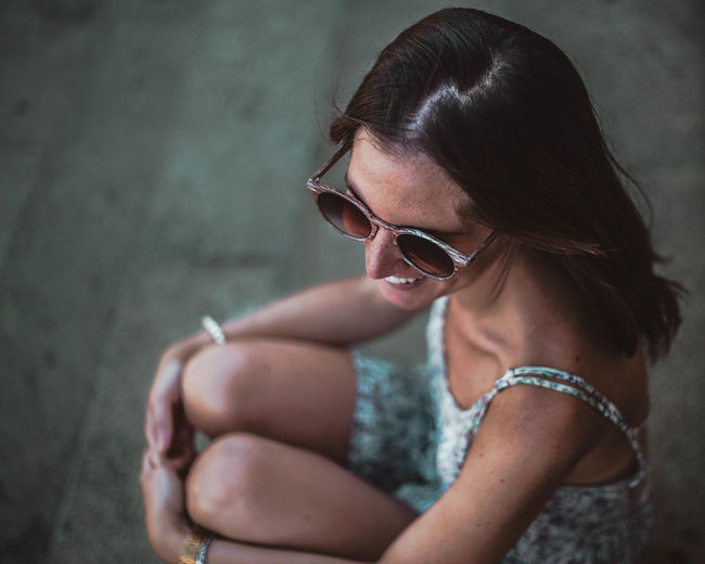 Woman wearing sunglasses while sitting in city