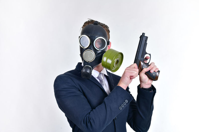 Well-dressed businessman wearing gas mask against white background