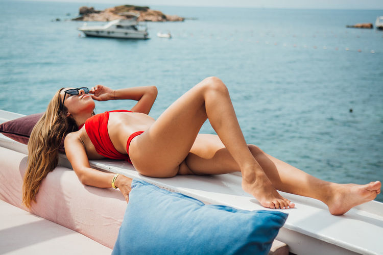 Lying Down Relaxation Water One Person Young Adult Lifestyles Sea Leisure Activity Real People Young Women Resting Lying On Back Full Length Day Adult Nature Swimwear Sun Beautiful Woman Outdoors