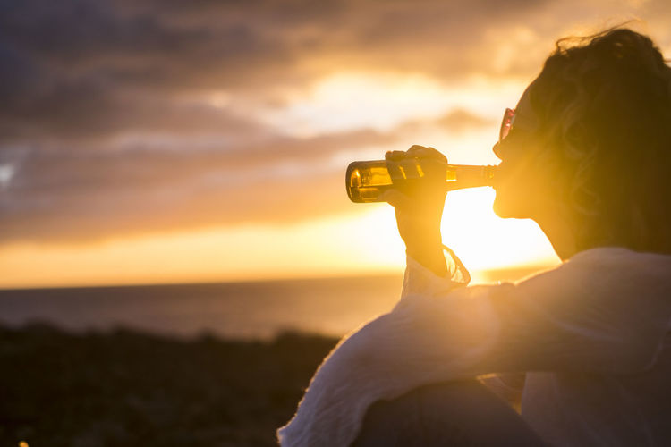Side View Of Mature Woman Drinking While Sitting Against Cloudy Sky During Sunset