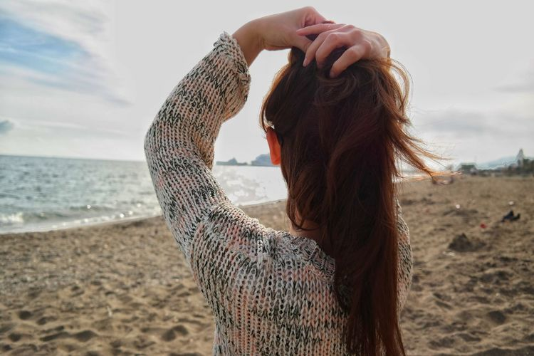 Woman with hand in hair at beach