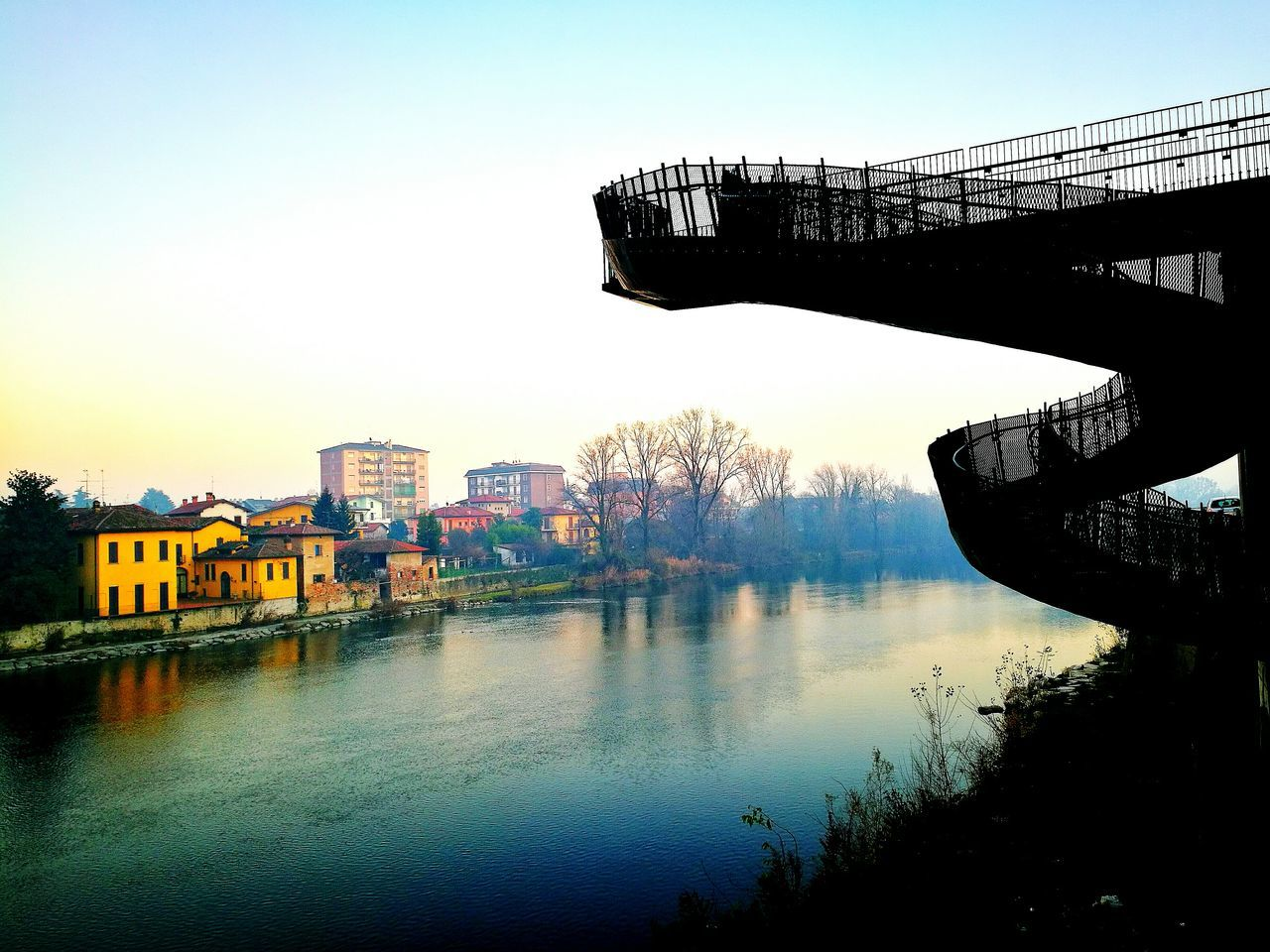 built structure, architecture, building exterior, water, river, reflection, outdoors, clear sky, no people, waterfront, bridge - man made structure, day, city, sky, nature, tree