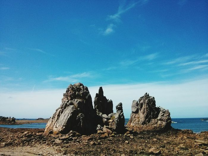 Rock formations at sea shore against blue sky