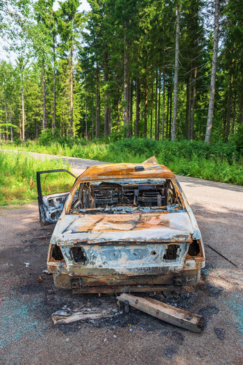 Abandoned car on road in forest