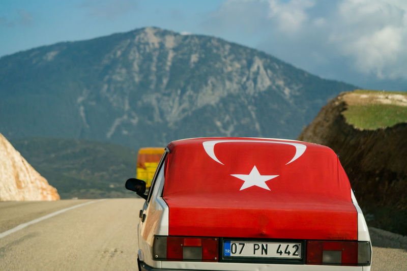 A common sight of a patriotic car owner decorating their car with a large Turkish flag. Beauty In Nature Communication Day Direction Environment Flag Mode Of Transportation Mountain Mountain Peak Mountain Range Nature No People Non-urban Scene Outdoors Red Red Flag Road Scenics - Nature Sign Sky Symbol Transportation Turkish Flag
