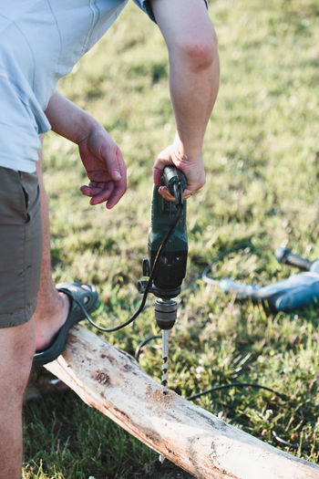 Man drilling hole in timber while working in garden Day Outdoors Working Work Builder Building Craft Carpenter Carpentry Construction Craftsman Garden Males  Man person Site Timber Wood Wooden Tool Artisan Casual Clothing Drill Drilling Holding Electrical Equipment Machine Electric Drill Bit