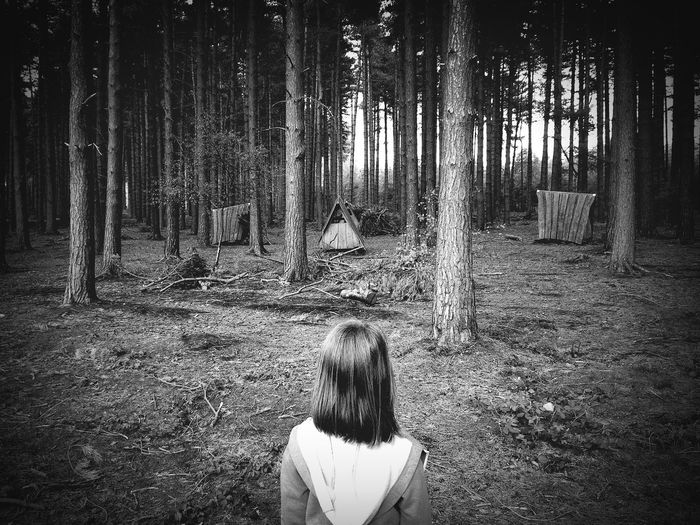 Rear view of girl at campsite in forest