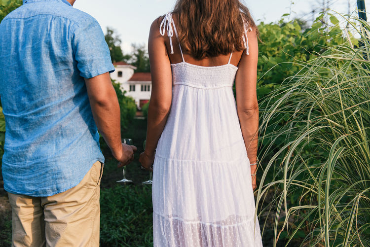 Rear view of couple standing against plants