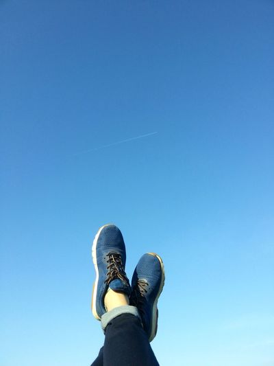 Low Section Of Person With Feet Up Against Blue Sky