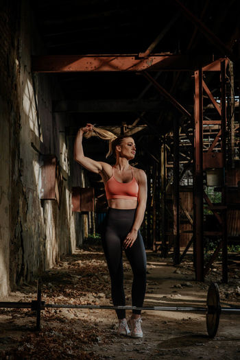 Full length of woman in sports clothing standing by barbell at abandoned building