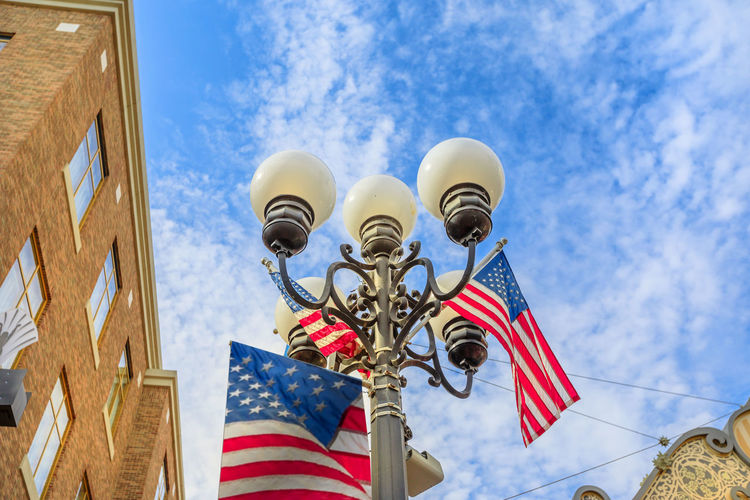 Typical vintage gas lamp with american flag, symbol of old historic victorian Gaslamp Quarter, in San Diego Downtown, California, United States. Urban city street view. Streetlight against blue sky. Gaslamp District Gaslamp Quarter San Diego San Diego Ca San Diego, California California Street Road Night Lamp Light City Lights Architecture Skyline Cityscape Low Angle View Sky Flag Patriotism Cloud - Sky Day No People Nature Built Structure Outdoors Building Exterior Blue Striped Building Street Light Shape