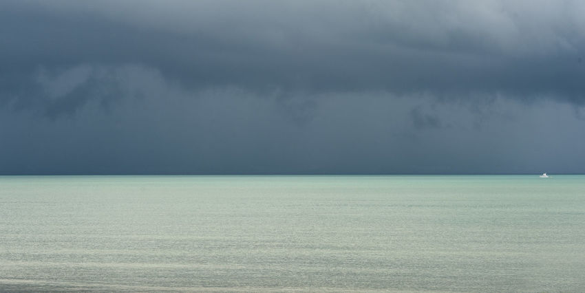 a panoramic ocean horizon with storm clouds and a small white boat Alone Backdrop Background Boat Calm Before The Storm Clouds Cloudy Flat Horizon Ispolated Light Lonely Plain Seascape Simple Composition Small Storm Stormy Stormy Weather