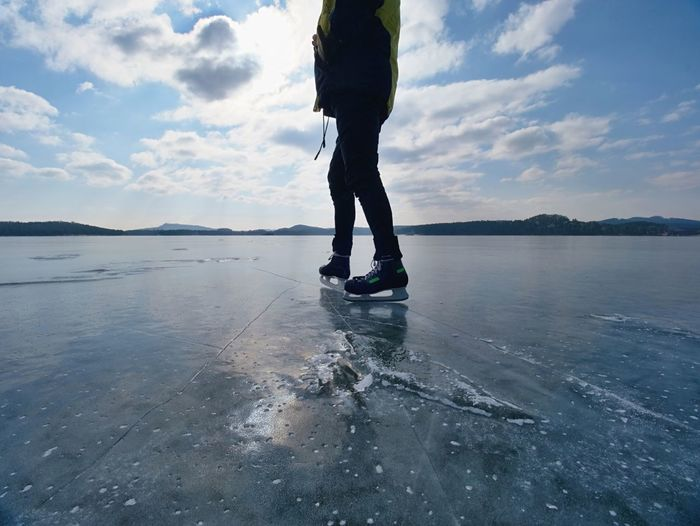 Silhouette of a boy skating on ice on lake against to winter sun.