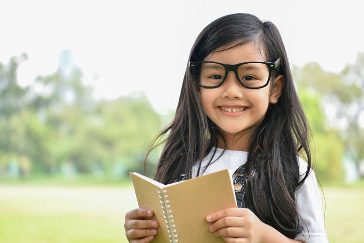 Portrait Of Smiling Girl Holding Book While Standing At Park