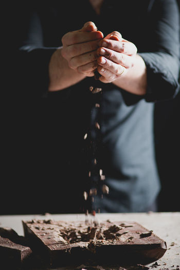 CLOSE-UP OF BAKER'S HANDS BREAKING CHOCOLATE