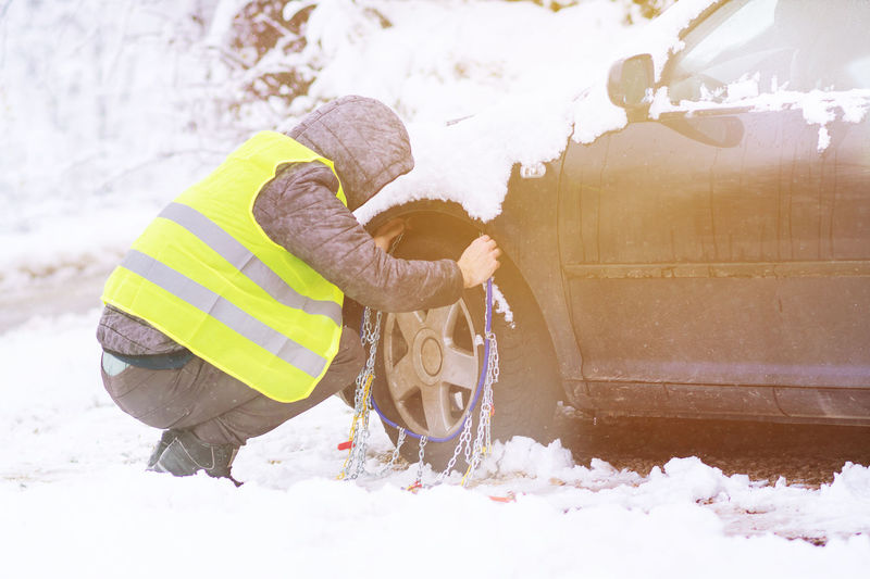 Man prepearing car for travelling at winter chains on the wheels of car. Bending Clothing Cold Temperature Covering Day Full Length Men Nature Occupation One Person Outdoors Real People Reflective Clothing Rescue Worker Snow Warm Clothing Winter Working