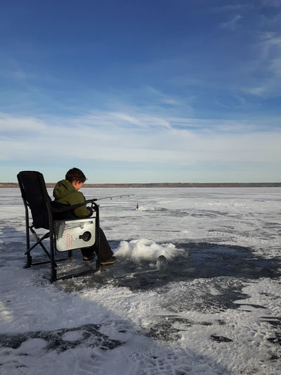 Boy ice fishing while sitting on chair against blue sky