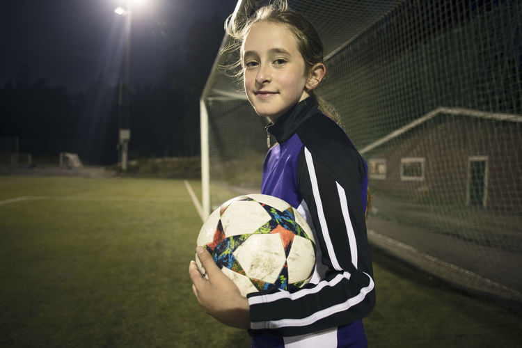 Portrait of girl holding ball on soccer field