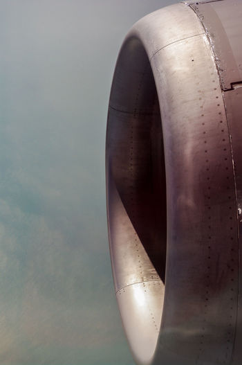 Close-up of airplane jet engine against sky