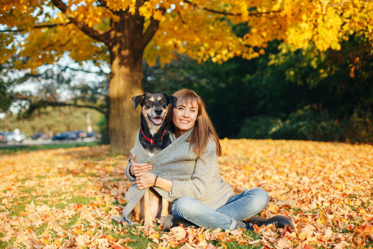 Portrait of young woman with dog sitting on leaves during autumn