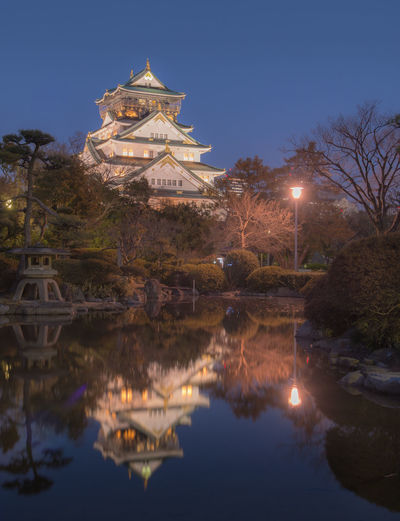 Himeji Castle in Osaka, Japan Water Reflection Illuminated Sky Nature Architecture Built Structure Building Exterior No People Lake Waterfront Religion Tree Belief Building Plant Spirituality Place Of Worship Night Outdoors