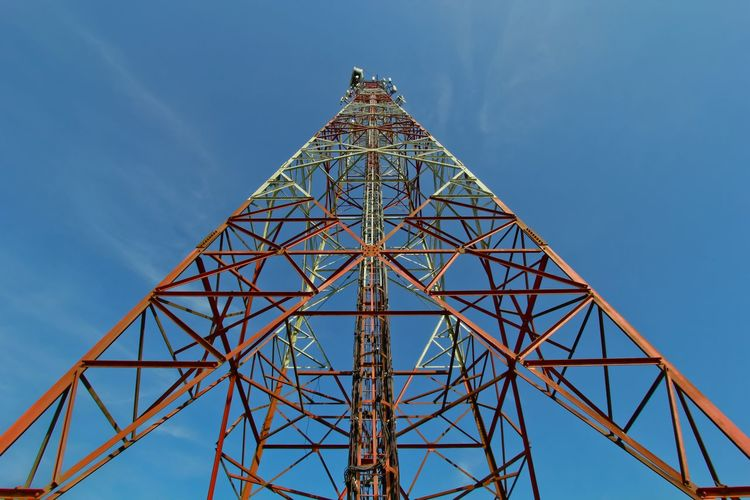 Low angle view of communication tower with blue sky