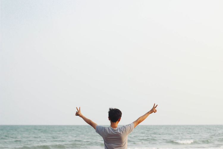 Rear view of man with arms raised against sea