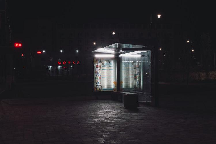 Illuminated bus stop on sidewalk at night
