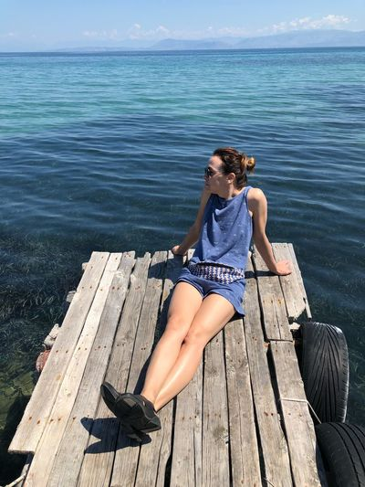Woman relaxing on pier over sea