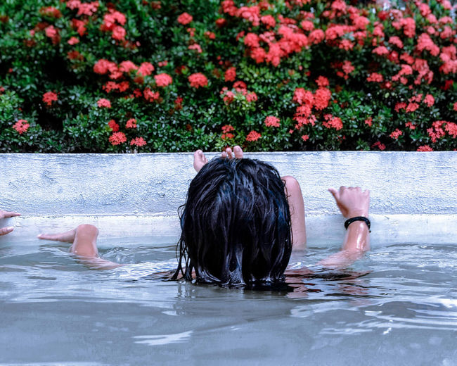 Rear view of girl swimming in pool against red flowers