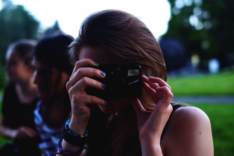 Close-Up Of Woman Photographing At Park