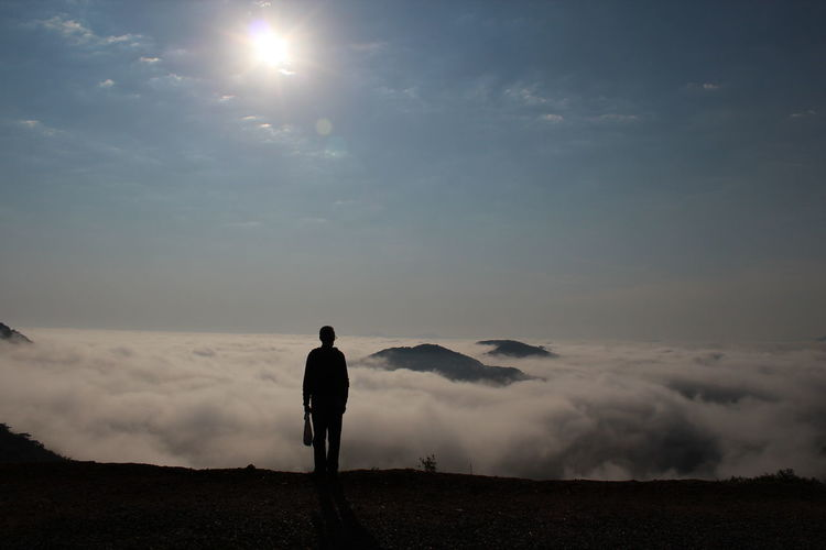 Rear view of man standing against cloudscape