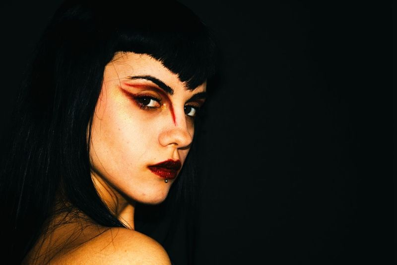 Side view portrait of serious young woman with eyeshadow against black background