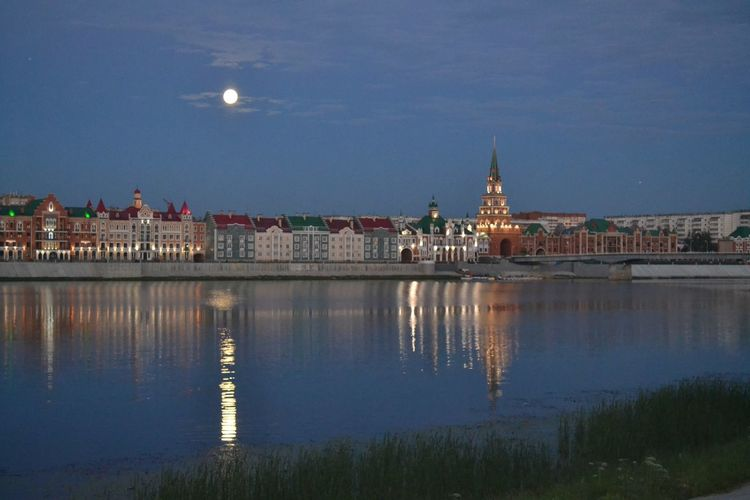Illuminated buildings by lake in city against sky