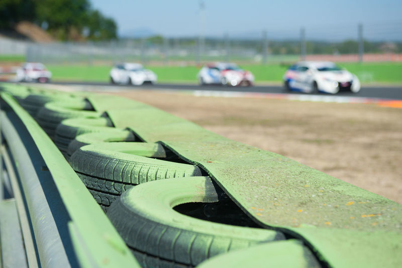 Green tires in row by railing against racecars moving on sports track
