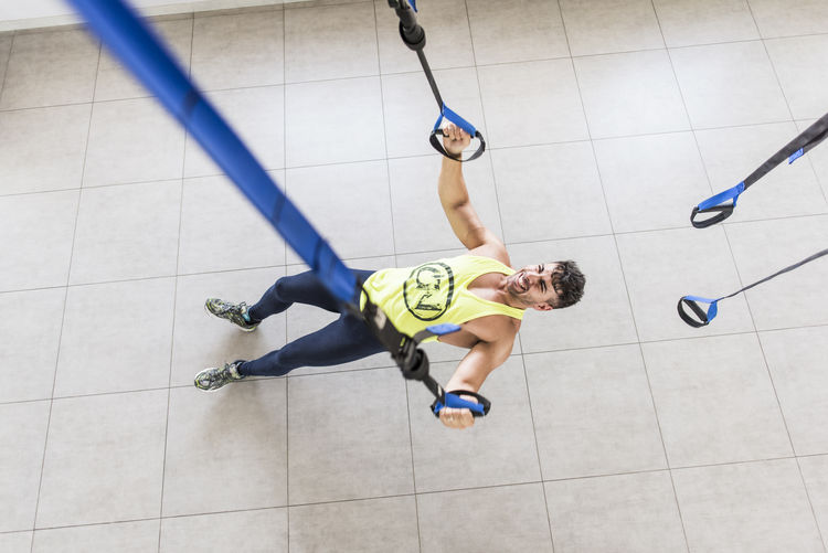 High angle view of man exercising on floor at gym