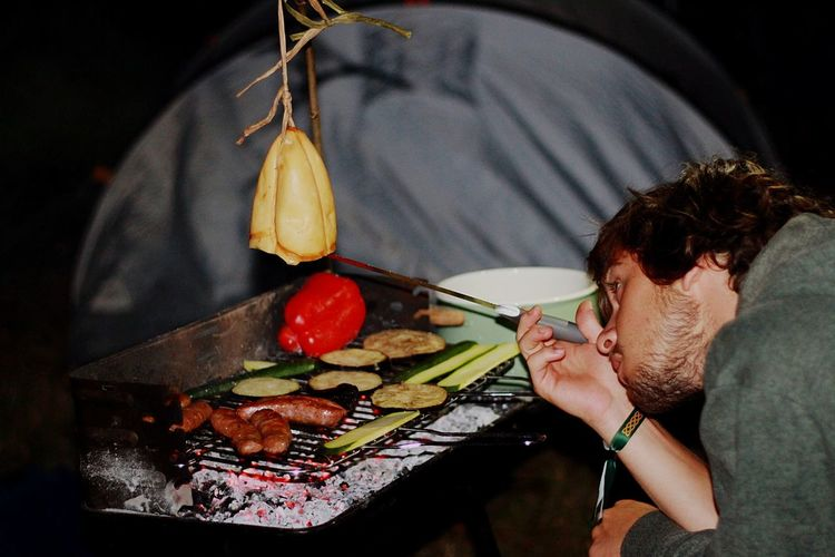 Young man preparing food over barbecue at campsite