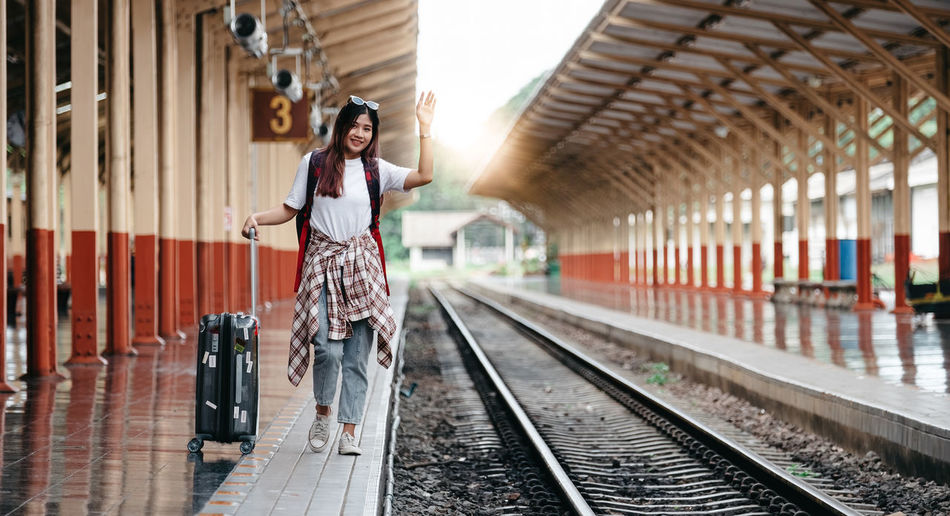 Portrait traveler asian woman walking and waits train on railway platform.