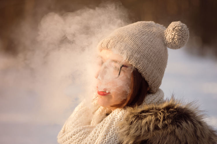 Smoking Adult Adults Only Beautiful Woman Blond Hair Close-up Cold Temperature Day Headshot Knit Hat Nature One Person One Woman Only Only Women Outdoors People Real People Scarf Vape Warm Clothing Winter Women Wool Young Adult Young Women