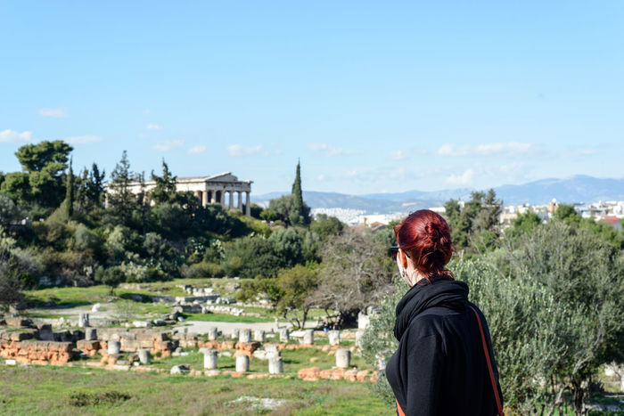View of an ancient Greek temple in the Agora over red haired girl's shoulder Agora Ancient Architecture Ancient Civilization Architecture Athens Athens, Greece Beauty In Nature Blue Built Structure Casual Clothing Day Grass Leisure Activity Mountain Nature Outdoors Relaxation Scenics Sky Tourism Tourist Tranquility Travel Destinations Tree Vacations