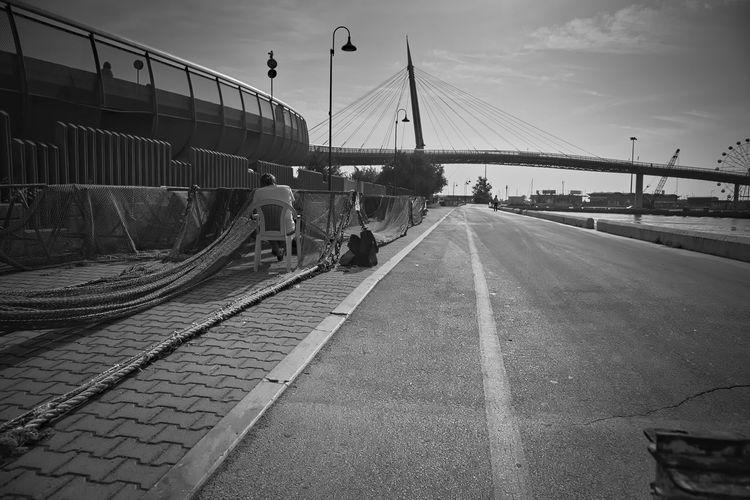 Railroad tracks by bridge against sky