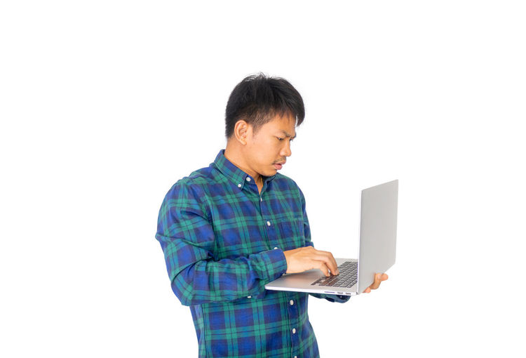 Mid adult man using smart phone against white background